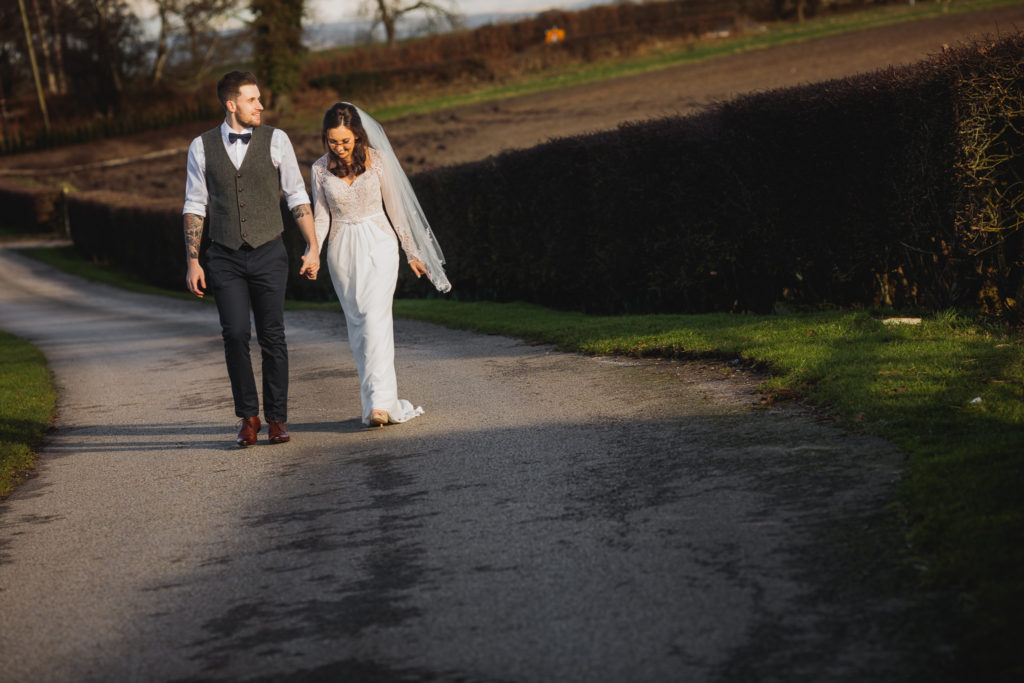 A wedding couple walk up the drive at Sandhole Oak Barn, Cheshire.